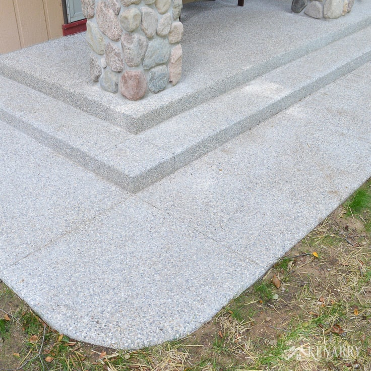 An exposed aggregate concrete walkway and steps around a large craftsman style front porch are low maintenance for an A-frame cottage home | home idea | outdoor patio | concrete steps
