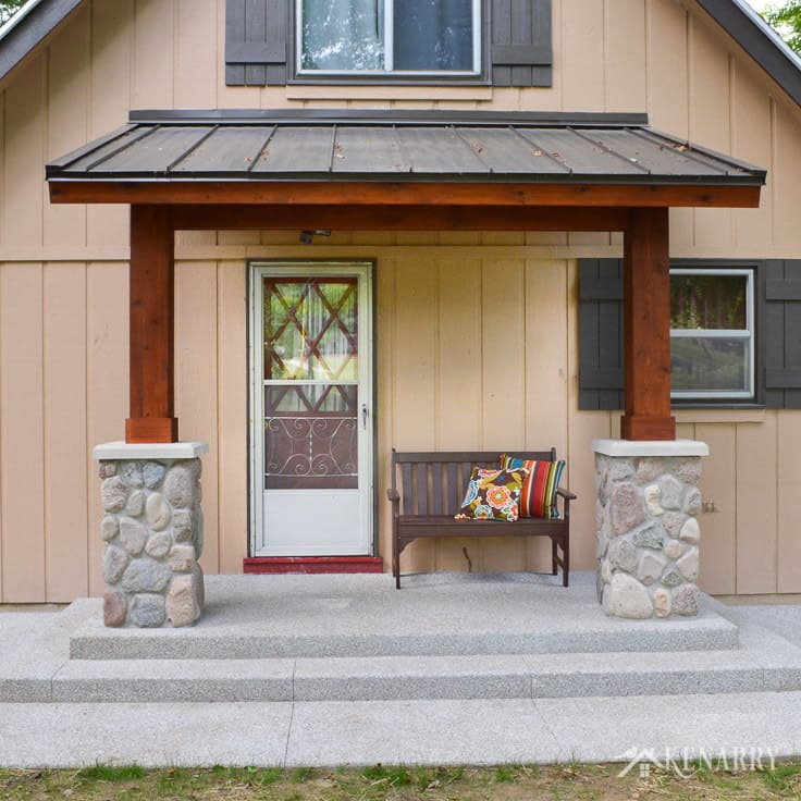 A sloped metal roof creates a covered front porch for an a-frame house or cottage. With cedar wood posts and river rock pillars for support, this exposed aggregate concrete patio gives this outdoor home idea beautiful craftsman style | mission bench | reverse board and batten siding