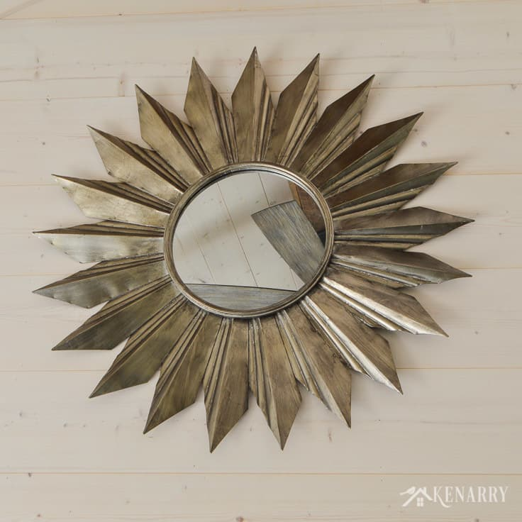 A large metal sunburst mirror on a shiplap wall in a cottage   industrial style   sunroom   shiplap walls   plank wall   whitewashed pine wood walls   home decor   home ideas   farmhouse style