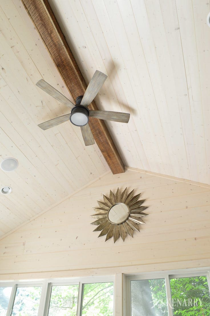 Exposed wood beam with a ceiling fan and a large metal sunburst mirror adds industrial style to this cottage home with vaulted shiplap ceiling and walls   sunroom   shiplap walls   plank wall   whitewashed pine wood walls   home decor   home ideas   farmhouse style
