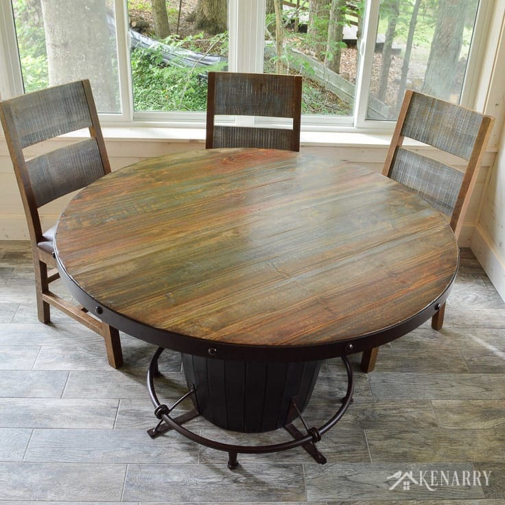 This round dining table with a barrel base and distressed chairs adds industrial style to a cottage sunroom - the antique multicolor round dining set from International Furniture Direct   dining room   shiplap walls   plank wall   whitewashed pine wood walls   porcelain tile floor   wood tile flooring   home decor   furniture   home ideas   farmhouse style