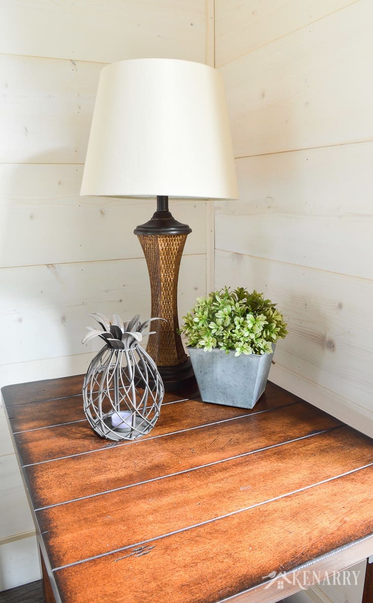 A rattan lamp and pineapple tealight candleholder and plant on a distressed industrial style side table add coastal style in a cottage sunroom with shiplap walls   sunroom   shiplap walls   plank wall   whitewashed pine wood walls   furniture   home decor   home ideas   farmhouse style