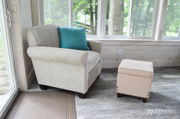 Angie Chair (#4634) from England Furniture in the color Perth Sand with a storage ottoman   cottage sunroom   footstool   hinged ottoman with storage   shiplap walls   plank wall   whitewashed pine wood walls   porcelain tile floor   wood tile flooring   home decor   furniture   home ideas   farmhouse style