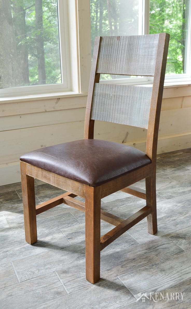 Distressed dining chair in a cottage sunroom - part of the antique multicolor round dining set from International Furniture Direct   dining room   shiplap walls   porcelain tile floor   wood tile flooring