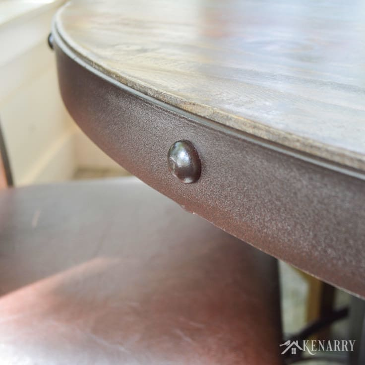 The iron edge of this round dining table adds industrial style to a cottage sunroom - the table is part of the antique multicolor round dining set from International Furniture Direct   dining room   farmhouse style