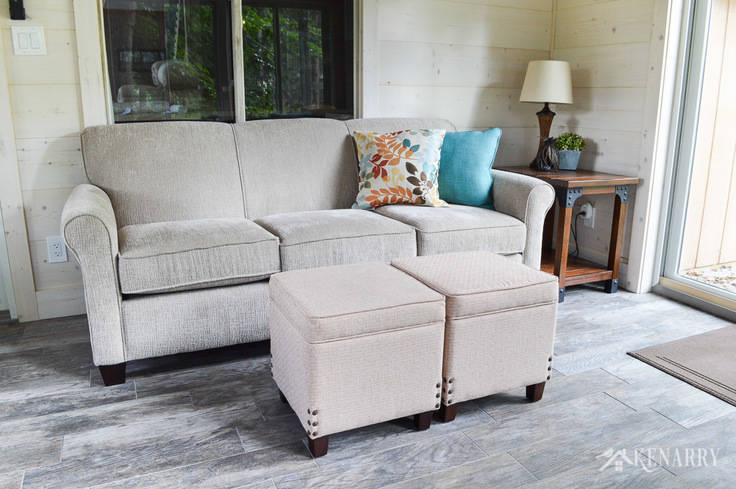 Put two together two upholstered footstools or ottomans to create a coffee table in a cottage sunroom   Angie Sofa (#4635) from England Furniture in the color Perth Sand   rattan lamp with side table   shiplap walls   plank wall   whitewashed pine wood walls   porcelain tile floor   wood tile flooring   home decor   furniture   home ideas   farmhouse style