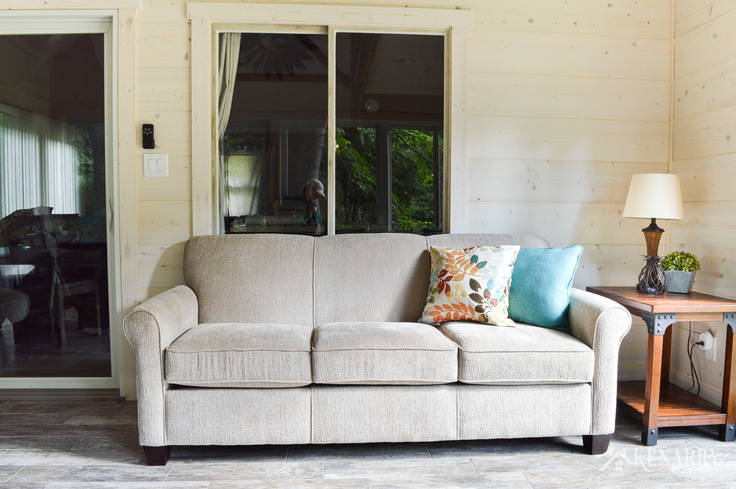 Angie Sofa (#4635) from England Furniture in the color Perth Sand in a cottage sunroom   rattan lamp with side table   shiplap walls   plank wall   whitewashed pine wood walls   porcelain tile floor   wood tile flooring   home decor   furniture   home ideas   farmhouse style