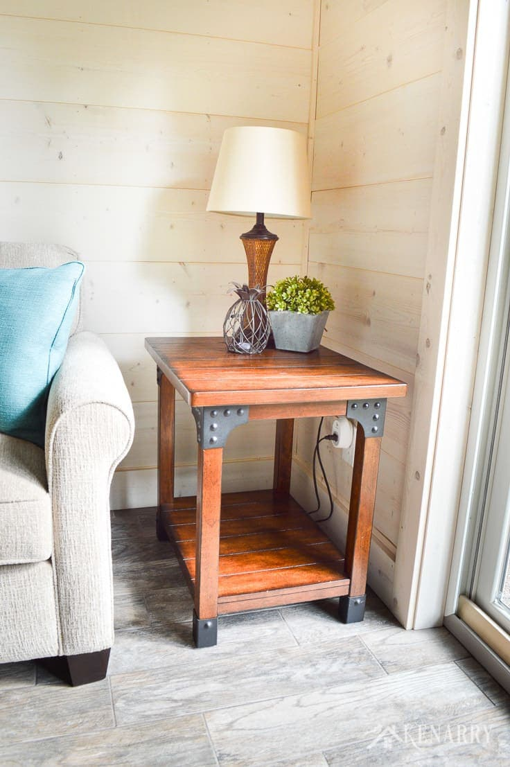 A distressed industrial style side table with a rattan lamp gives farmhouse style to a cottage sunroom with shiplap walls   plank wall   whitewashed pine wood walls   furniture   home decor   home ideas