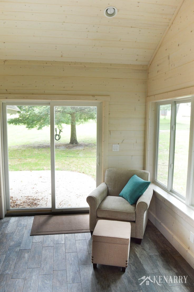 Vaulted ceiling above Angie Chair (#4634) from England Furniture in the color Perth Sand with storage ottoman   glass sliding door   cottage sunroom   footstool   hinged ottoman with storage   shiplap walls   plank wall   whitewashed pine wood walls   porcelain tile floor   wood tile flooring   home decor   furniture   home ideas   farmhouse style