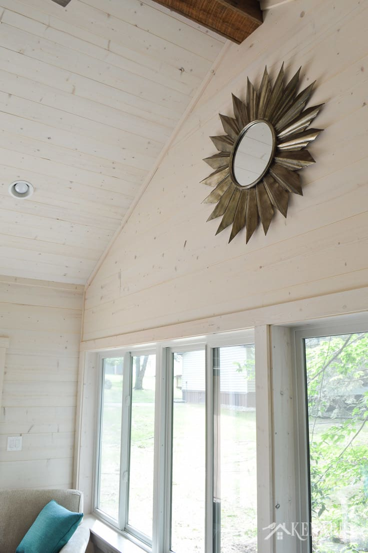 A vaulted ceiling with shiplap walls and a large metal sunburst mirror add industrial style to a sunroom in a cottage   shiplap walls   plank wall   whitewashed pine wood walls   home decor   home ideas   farmhouse style