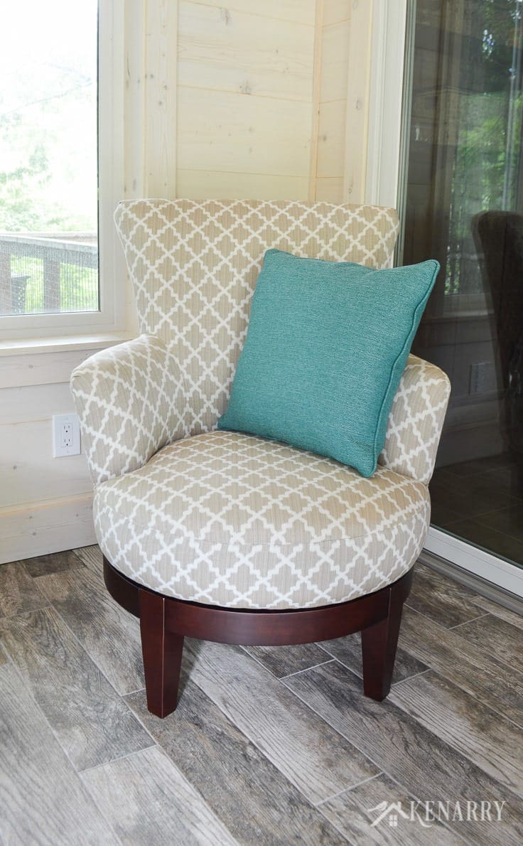Justine side chair from Best Home Furnishings in Silver 28843 with a DePalma Ocean turquoise or teal throw pillow from England Furniture   cottage sunroom   glass sliding door   footstool   hinged ottoman with storage   rattan lamp with side table   shiplap walls   plank wall   whitewashed pine wood walls   porcelain tile floor   wood tile flooring   home decor   furniture   home ideas   farmhouse style