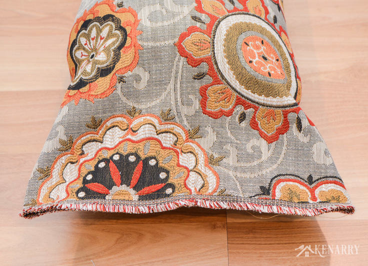 Colorful upholstery fabric with fringe adds a decorative touch to a fireplace draft protector. You can sew a body pillow case yourself to make a DIY draft blocker to help save heating costs and block cold air this winter. draft stopper | draft protector | draft excluder | door draft blocker
