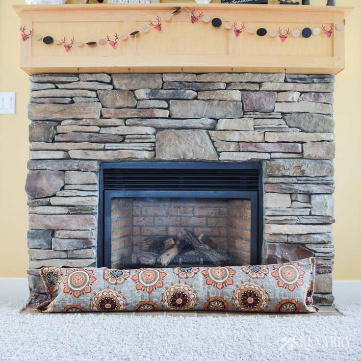 Learn how to make a fireplace draft stopper. It's a great way to upcycle an old body pillow you're not using any more. Plus by sewing your own draft blocker, you can save heating costs and block cold air this winter. draft stopper | draft protector | draft excluder | door draft blocker