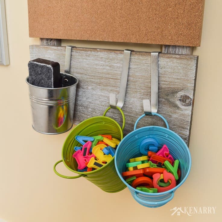 Colorful metal storage containers are great for holding magnetic letters or a dry eraser so kids can get to them easily. These are a small part of the playroom wall decor in a larger gallery wall designed for children.