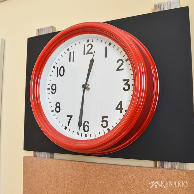 A bright bold red clock helps kids learn to tell time when it's used as playroom wall decor. This one is part of a gallery wall in a colorful children's playroom.