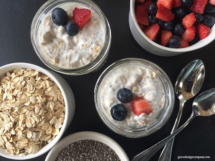overnight oats in mason jars topped with strawberries and blueberries
