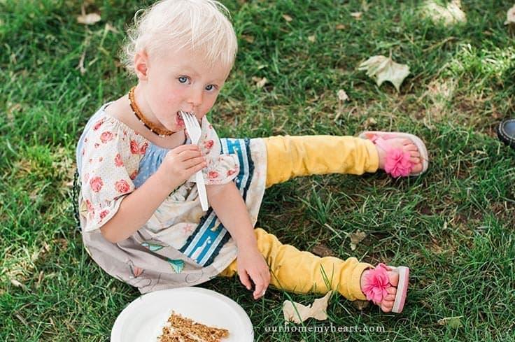 little girl sitting on grass eating a lice of allergy friendly carrot cake