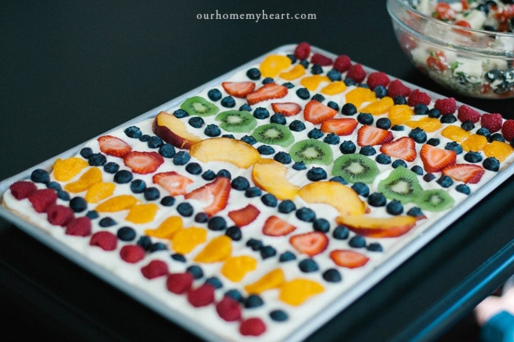 A fruit pizza with strawberries, blueberries, mandarin oranges, and kiwis on it.