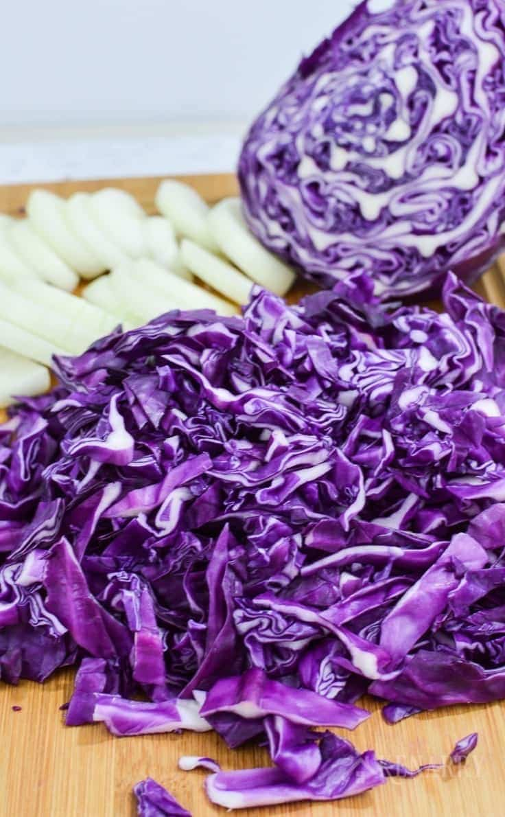 chopped red cabbage and onions on a cutting board