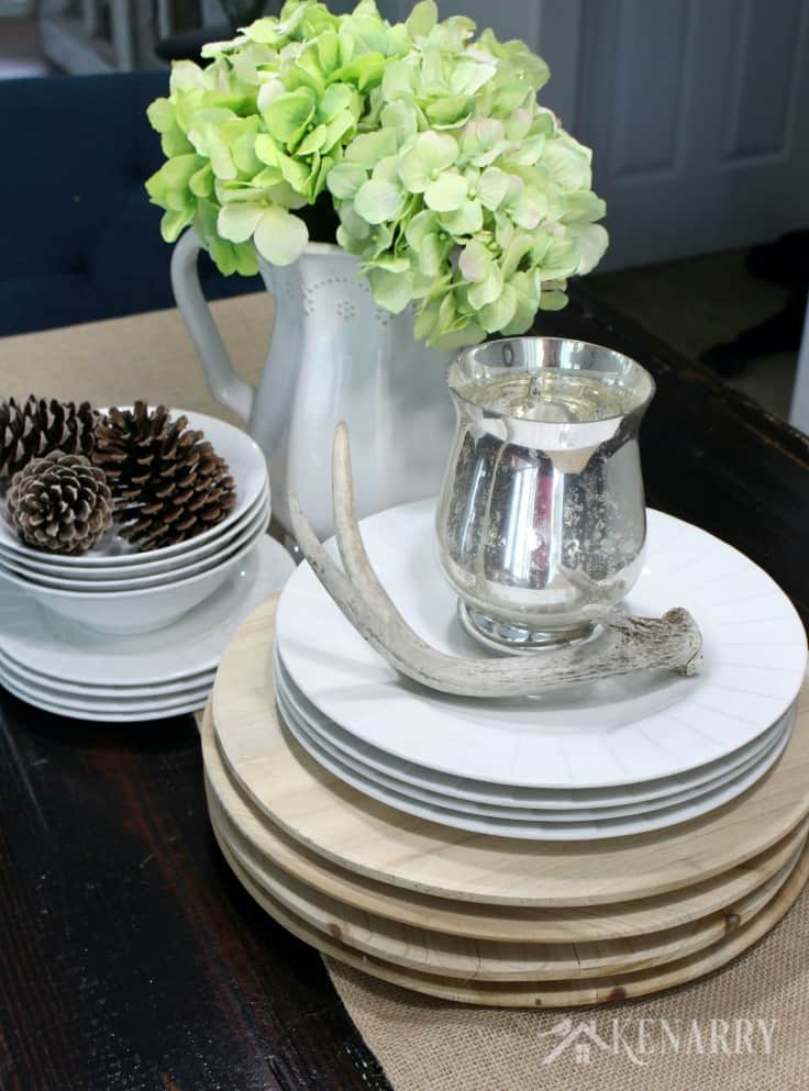 Use pinecones, antlers, white dishes and wood chargers along with a burlap table runner as Thanksgiving table decor to give your holiday dinner rustic farmhouse style.