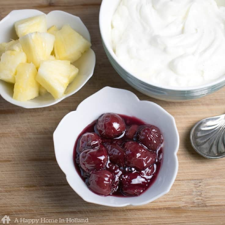 Dutch hangop in a bowl along with bowls of canned cherries and pineapple