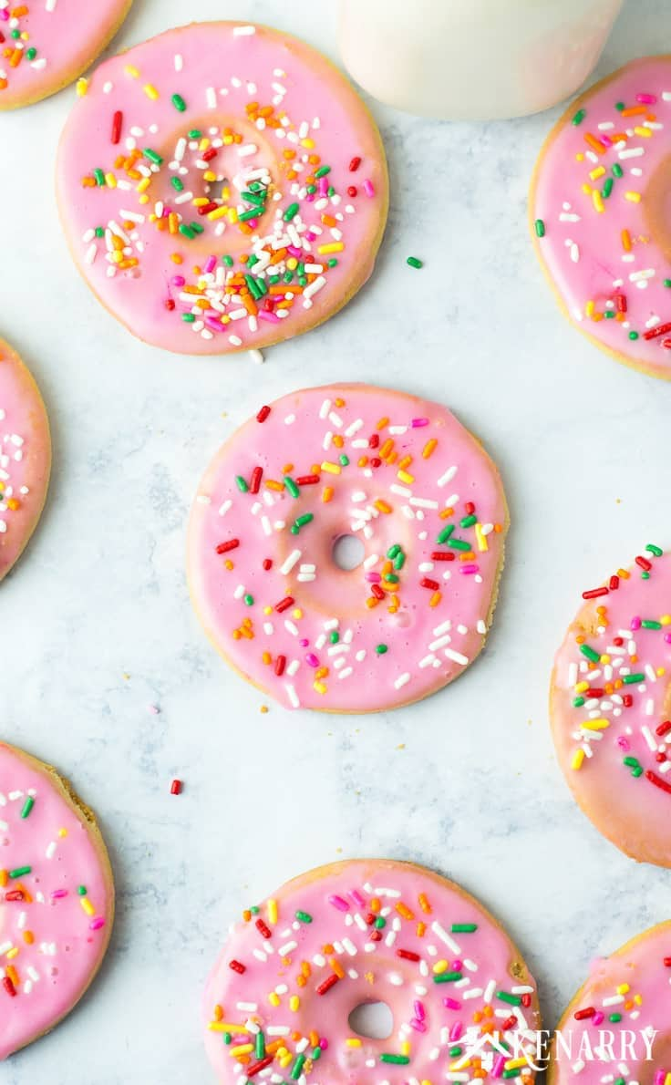 cookies shaped and decorated like pink donuts with sprinkles on top
