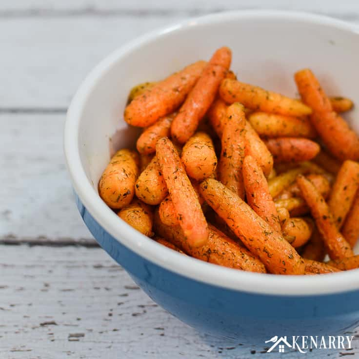 roasted carrots with dill in a bowl on a wooden surface