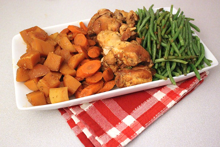 Slow Cooker Honey Garlic Chicken and Vegetables on a white serving dish on a red plaid towel