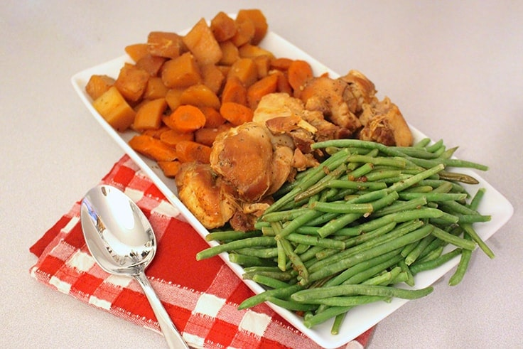 Slow Cooker Honey Garlic Chicken and Vegetables on a white serving dish on a red plaid towel with a spoon