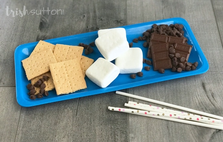 The ingredients you need to make Chocolate Dipped S'mores on a Stick - graham crackers, marshmallows, chocolate, sticks.