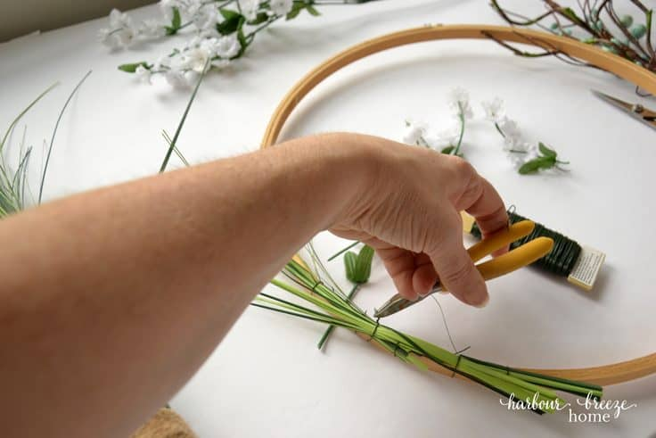 twist wire around faux greenery to attach it to an embroidery hoop wreath