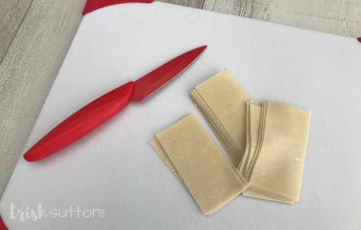 Cutting wonton wraps to make baked cinnamon chips.
