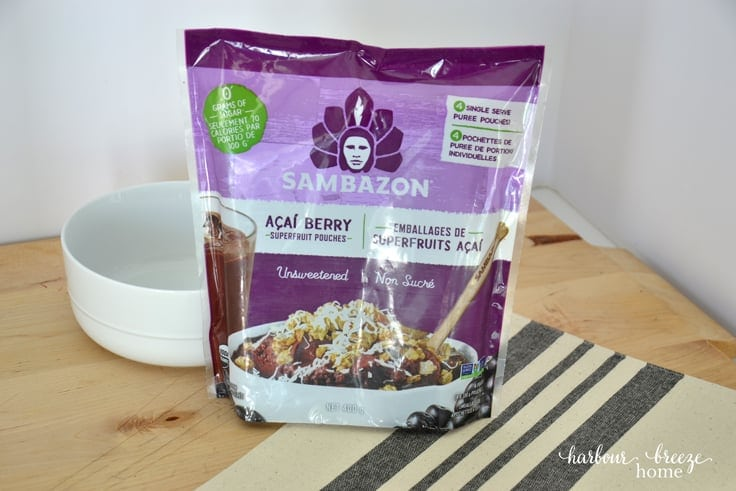 purple package of frozen acai berry packets for making açaí smoothie bowls sitting on a table with a gray striped cloth underneath