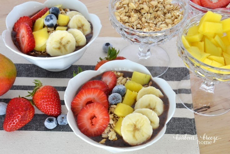 White bowls filled with acai berry smoothie and topped with strawberries, granola, mango, banana and blueberries