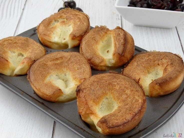 popovers in a muffin tin on a white wood surface