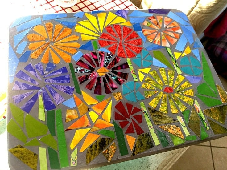 Bright paper shapes glued to a stool that looks like mosaic flowers.