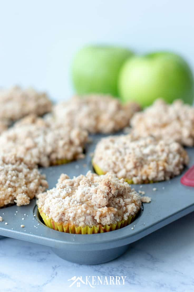 apple coffee cake muffins in a muffin tin with green apples in the background