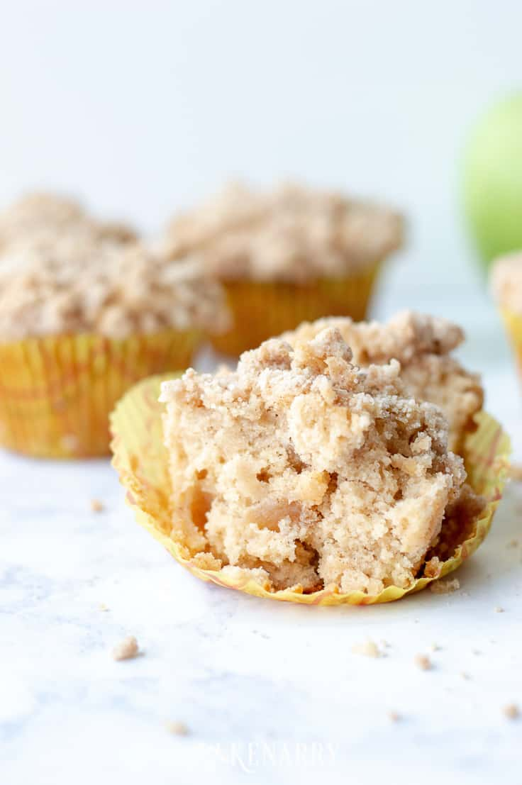 partially eaten apple coffee cake muffins on a marble surface with green apples in the background