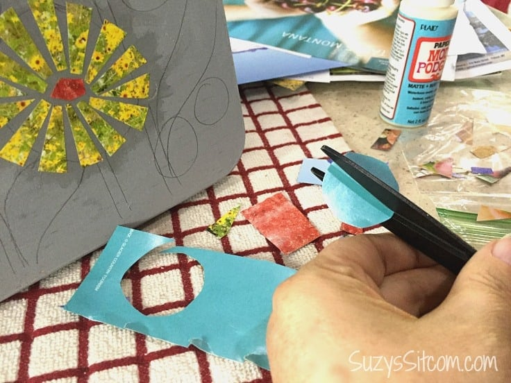 Cutting out paper that you will mod podge onto a stool.