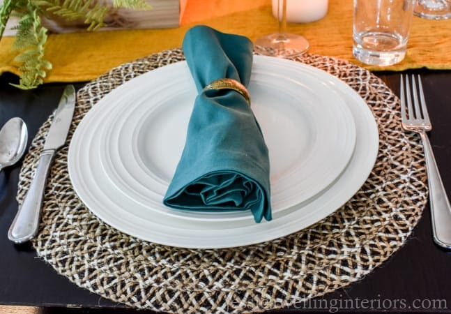 A round placemat with plates and a napkin on top