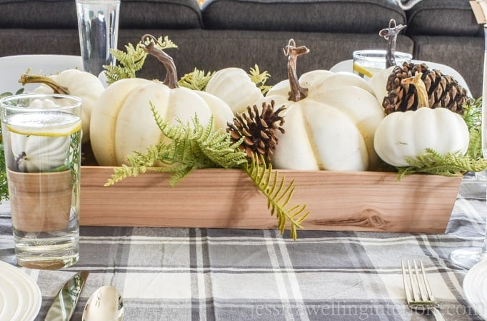 A close up of white pumpkins in a box being used as a Thanksgiving table centerpiece