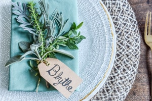 photo of place setting with simple place card holder with fresh herbs