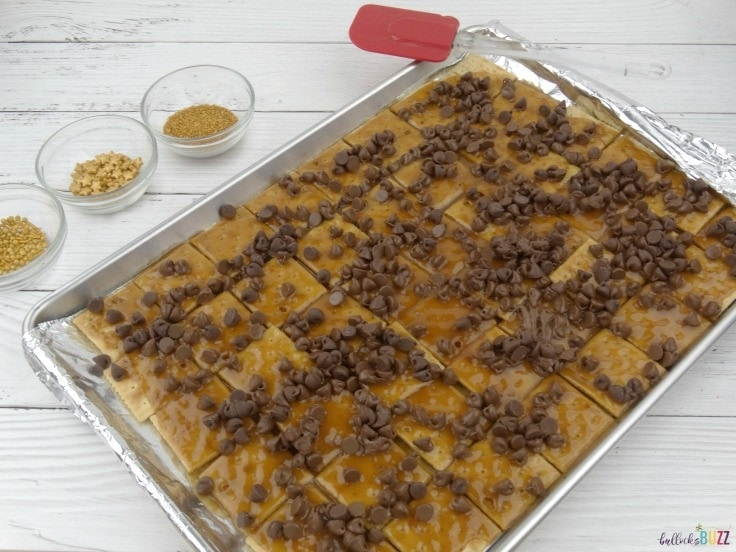 Add chocolate chips on top of toffee for New Year's Eve Toffee Bark