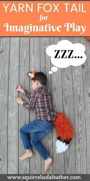 A boy sleeping in a yarn fox tail costume.