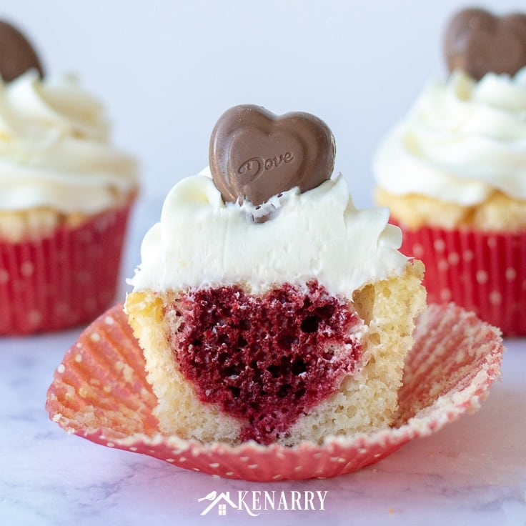 Surprise your sweetheart with festive Valentine's Day Cupcakes. This fun dessert idea has a hidden red velvet heart inside each of these delicious treats.