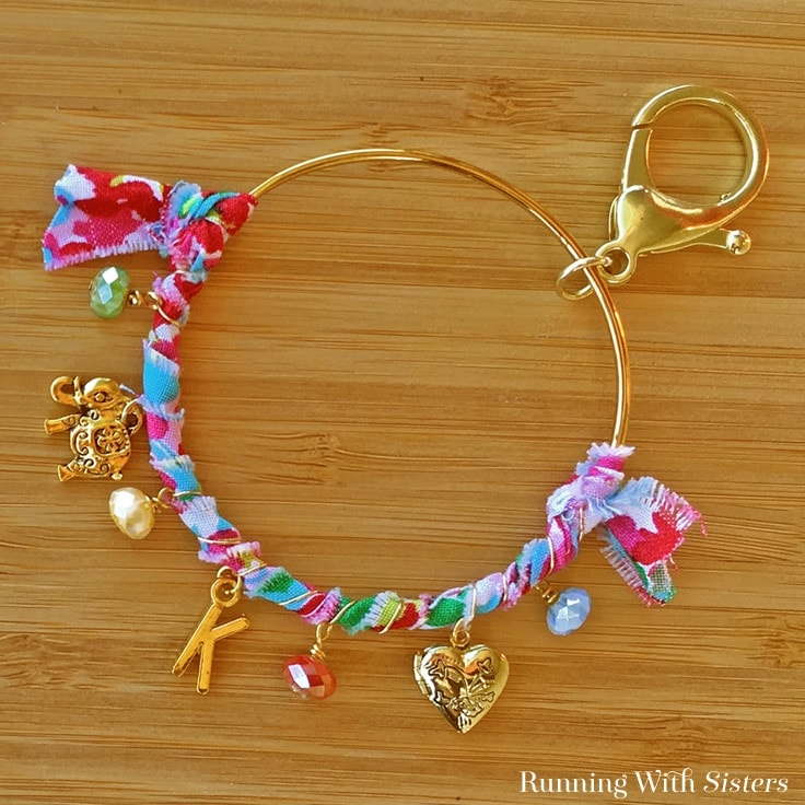 Make a DIY Monogram Charm Keychain to give as a handmade gift or keep for yourself! It's easy to personalize this boho keychain with colorful fabric, beads, and charms. Click through to watch the video tutorial and learn how to make it now! #handmadegifts #diycrafts #kenarry