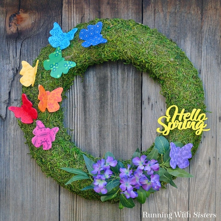 Make an easy Spring Butterfly Wreath for your front door with colorful butterflies! We'll show you how to decoupage wood butterflies with fabric to make your own DIY wreath. #springcrafts #spring #kenarry