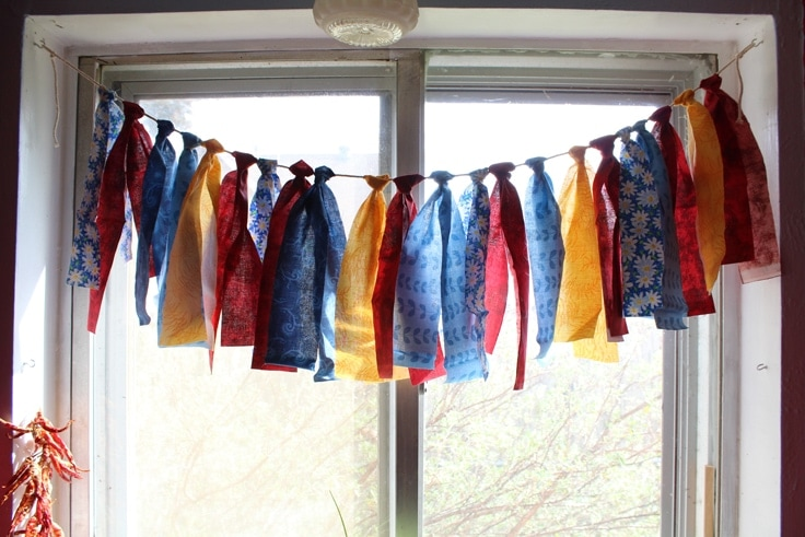 DIY Fabric garland is an easy craft project that uses up fabric scraps from your stash. It's so simple you'll want to make it for dressing up windows, decorating for a party, or just to swap out your color scheme for a season.
