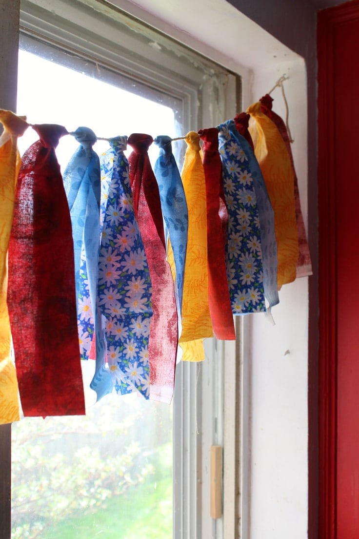 This DIY Fabric garland or banner is an easy craft project that uses up fabric scraps from your stash. You'll want to learn how to make it for dressing up a nursery or bedroom, decorating for a party, or just to swap out your color scheme for Christmas or any other season. #easycrafts #garland #kenarry