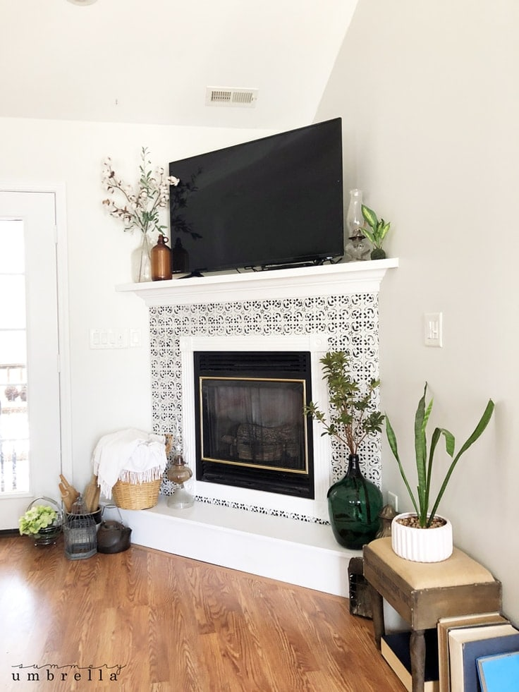A white corner fireplace with DIY faux tiles painted on it.